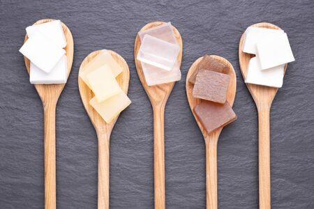 Five kinds of glycerin soap bases on wooden spoons on black stone background