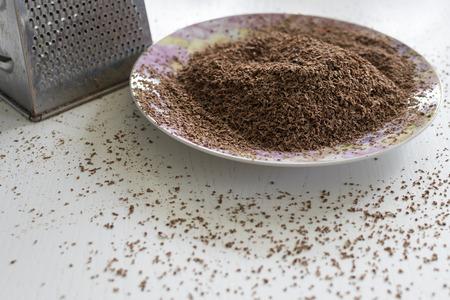 Chocolate grated on a fine grater. Lies on a plate. Stock Photo