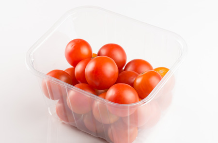red cherry tomatoes in a transparent plastic box Banco de Imagens