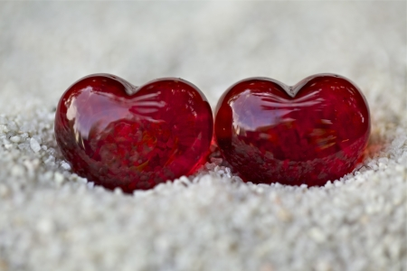 Two red hearts with stones on the sand photo