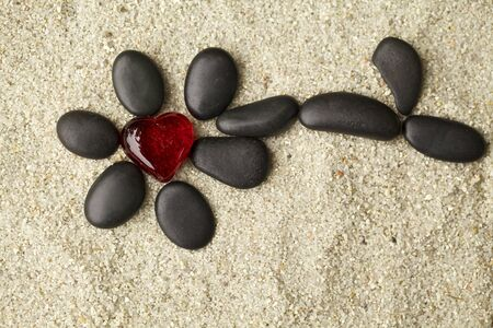 Flower of black pebbles on the sand   photo
