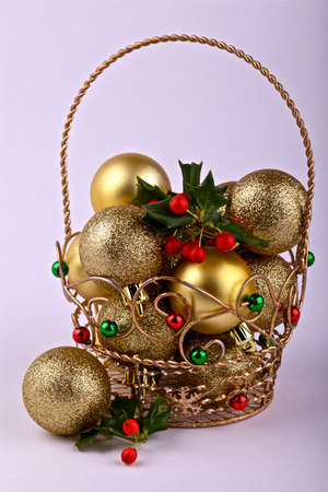 Christmas baubles in a decorative basket on background photo