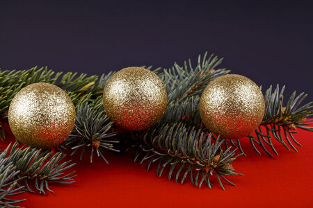 Christmas card,gold baubles and fir twigs on a red and black background photo