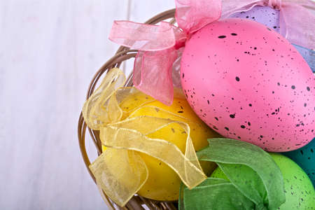 Easter decorative eggs in the basket on light background Stock Photo