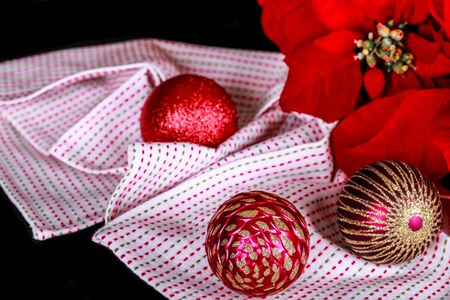Christmas decoration, red poinsettia, christmas bauble and fabric on a black background. Stok Fotoğraf