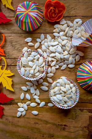 Roasted salted pumpkin seeds in paper molds a little seeds scattered on a wooden table. Colorful image seen from above, autumn decoration