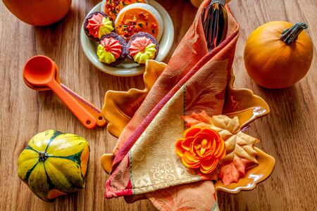 Thanksgiving fall table place setting with cutlery, pumpkins, cookies. Top view on a wooden table. Stok Fotoğraf