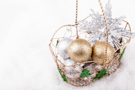Christmas decoration, star and baubles in a decorative basket.