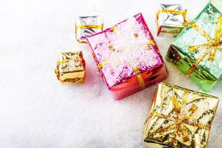 Six colorful glossy gift boxes on a snowy background. Stok Fotoğraf