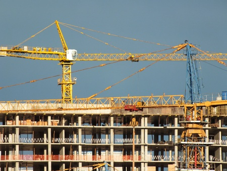 uncompleted: Two construction cranes with an uncompleted building Stock Photo