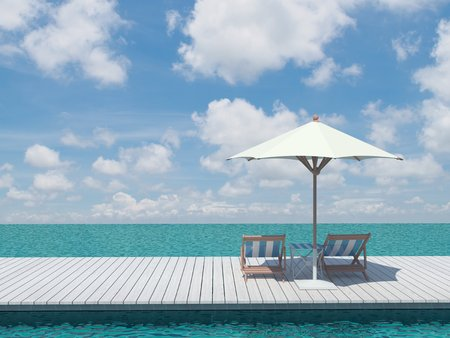 view of two chairs and white umbrella on the wood pier on the shore near the sea  photo