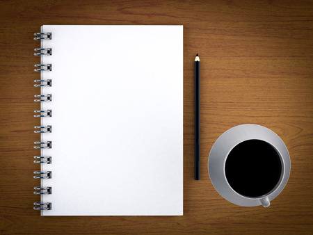 notepad with coffee cup on wood table photo