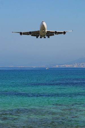 passing over: Plane passing over a beach Stock Photo
