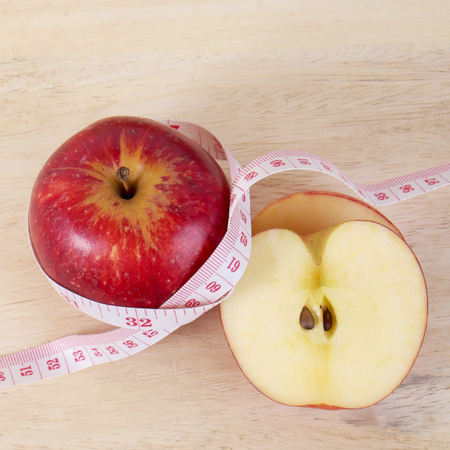 centimeter: Red apple with centimeter on wood table for diet concept