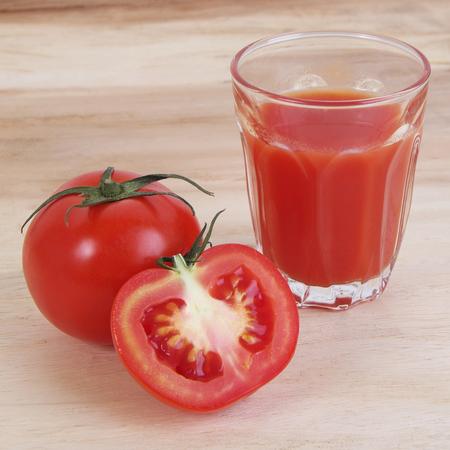 jugo de tomate: Jugo de tomate en el fondo de madera Foto de archivo