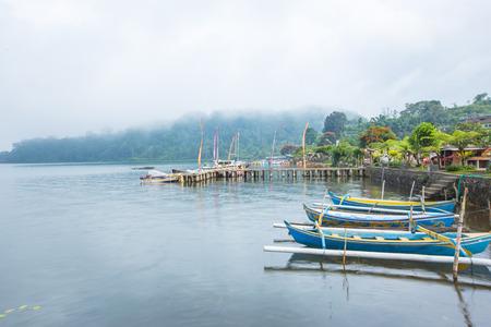 ship and mountain on river near ulun danu temple, bali , indonesia