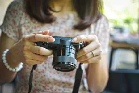Cropped image of young female traveler watching the photo in mirrorless camera. Aisan woman taking photo using dslr camera. Selective focus Foto de archivo - 133743132