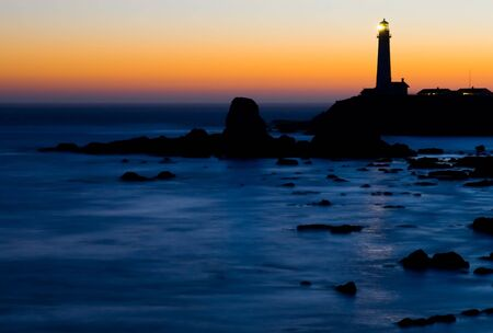 lighthouse with beam: Pigeon Point Lighthouse in California at night right after sunset