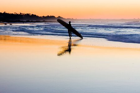 Silhouette of surfer at sunset photo
