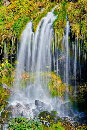 Waterfall in the mountains in autumn photo