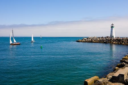 Lighthouse and sail boats photo