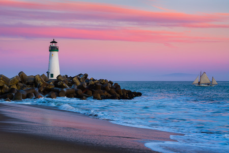 sea port: Santa Cruz Breakwater Lighthouse in Santa Cruz, California at sunset Stock Photo