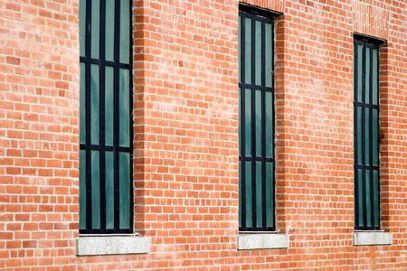 Three windows in old restored red brick building. Stock Photo