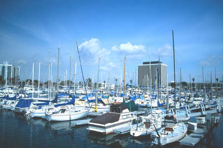 Marina full of boats with buildings in the background against blue sky and clouds. Imagens