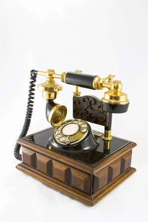 Old styled telephone on a wooden base with a white background.