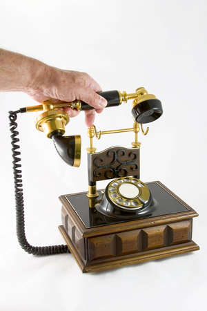 Old styled telephone on a wooden base with the receiver in a males hand.