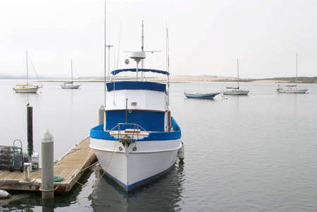 A powerful small size fishing boat tied to the marina dock.