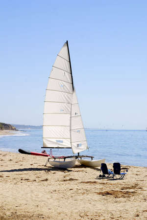 A catamaran, raft and two beach chairs on a deserted beach denotes seclusion. Imagens