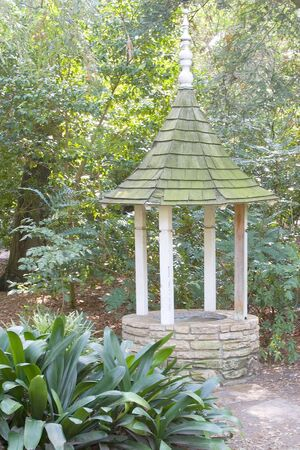 An old wishing well, in need of repair, tucked in a shady part of a garden. Imagens