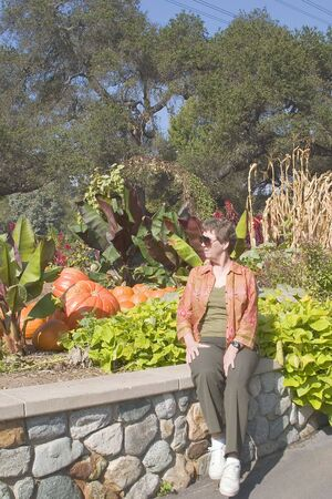 After a day of walking in a public garden, a mature woman takes a rest by an autumn display.
