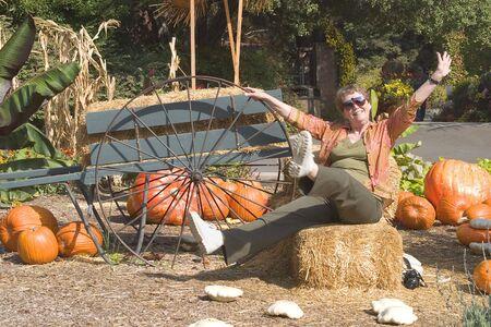 Mature woman having fun playing around in an autumn display.