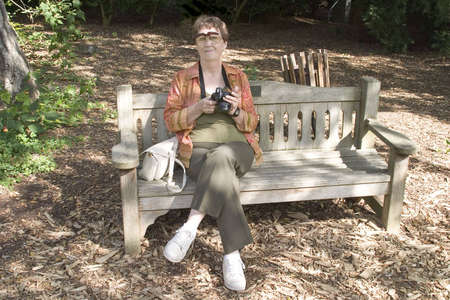 Mature woman seated and enjoying being a part of the outdoors in autumn.