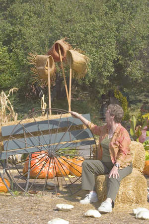 Mature woman seated enjoying being a part of a colorful autumn display.