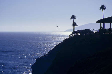 Silhouette of a tropical hut on a cliff overlooking the ocean.