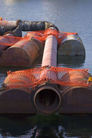 Harbor dredging pipes being held by barrels waiting to be used.