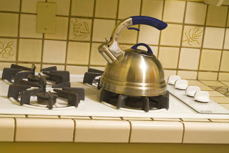 Kettle on an old stove burner boiling water for tea.