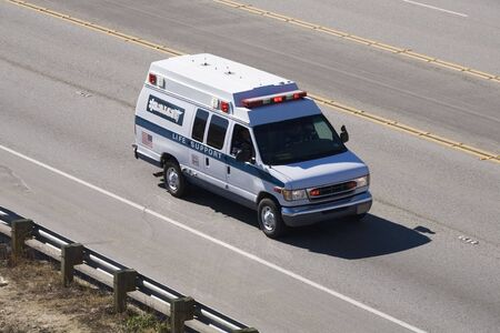 An ambulance is raising down the highway to give medical assistance to an injured person.