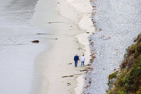 A middle aged couple walking along the beach remembering the past and dreaming about the future. Imagens