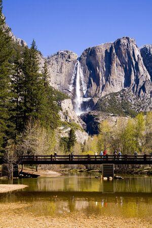 Bridge across a small creek below a high waterfalls