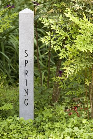 Granite sign post designating the spring season surrounded by plants.