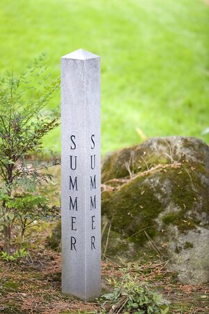 Granite sign post designating the summer season surrounded by grass.