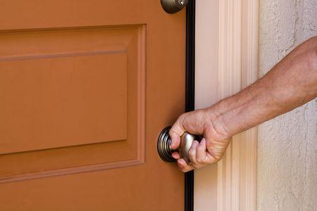 Man het openen van de deur van zijn huis.