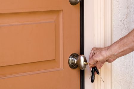 Homeowner unlocking the front door to his house. photo