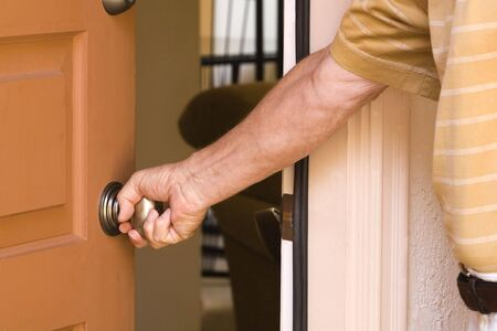 door knob: Man opening the front door of his home, saying