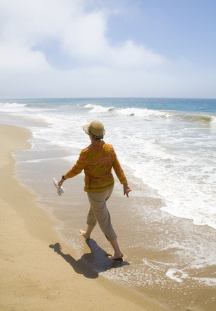 mature woman walking on the beach on a clear, cool day.