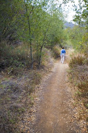 Mature woman hiker on hiking trail in bushy area. Imagens